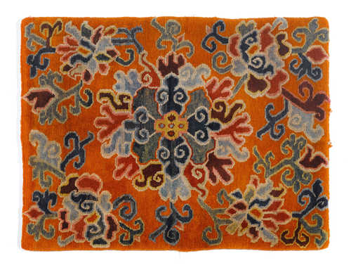 A SEATING CARPET WITH FLORAL DECORATION ON AN ORANGE GROUND.