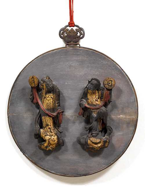 A WOOD ROUNDEL WITH TWO IMMORTALS HOLDING SUN AND MOON.