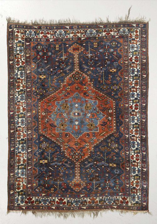 BIDJAR antique.Blue ground with medallions in red and light blue, patterned with stylized flowers, white border with trailing flowers, slight wear, 175x225 cm.