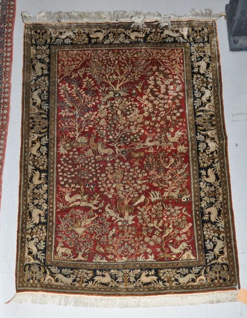 GHOM SILK old.Dusky pink central field finely patterned with plants and animals, black border, 105x158 cm.