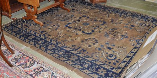 CHINESE antique. The light brown central field is patterned with floral motifs in blue and white. The dark blue border has trailing flowers. Stained, with slight wear, 245x286 cm.