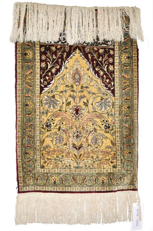 HEREKE PRAYER RUG.The beige Mihrab is decorated with a tree of life and red spandrels. With a light green border. Slightly worn, 57x80 cm.