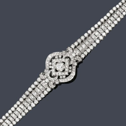DIAMOND BRACELET, ca. 1950. White gold 750. Classic-elegant, three-row bracelet set throughout with numerous brilliant-cut diamonds, the centre additionally decorated with 1 florally open-worked ornament set with 1 brilliant-cut diamond of ca. 0.50 ct. In total: ca. 220 brilliant-cut diamonds weighing ca. 9.00 ct. L ca. 18 cm.