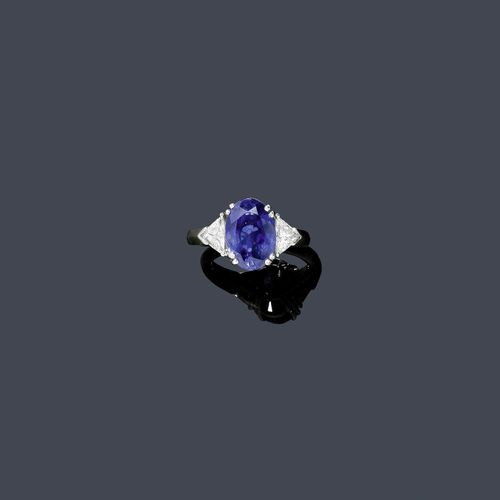 SAPPHIRE AND DIAMOND RING. White gold 750. Classic ring, the top set with 1 oval sapphire of 6.07 ct, untreated, flanked by 2 triangle-cut diamonds weighing ca. 0.96 ct. Size ca. 51, shank slightly oval. With Jeweller's certificate, February 2010 and Gübelin Report No. 0601015, January 2006.