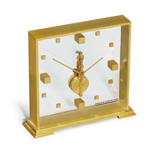 TABLE CLOCK WITH STICK MOVEMENT, JAEGER LE COULTRE, ca. 1980. Brass. Square, glass-covered brass case No. 553 with visible, vertical movement. Signed on the glass. Stick movement, Cal. 210/1. Ca. 15 x 15 cm, without base. With copy of the warranty, December 1979.
