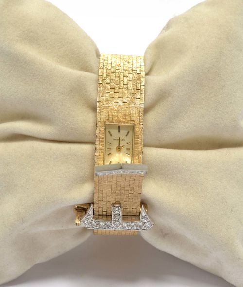 "DIAMOND AND GOLD BRACELET WATCH, 1950s. Yellow gold 585, 45g. ""À ceinture"" model with hidden watch. Decorative, satin-finished brick-pattern bracelet, the clasp and end pavé-set with 28 brilliant-cut diamonds weighing ca. 0.50 ct. Rectangular case No. 11346 engraved C+B. Silver-coloured dial signed Tiffany & Co. with gold-coloured indices and hands. Form movement No. 489PH, Cal. FHF59-21 signed Concord Watch Co."