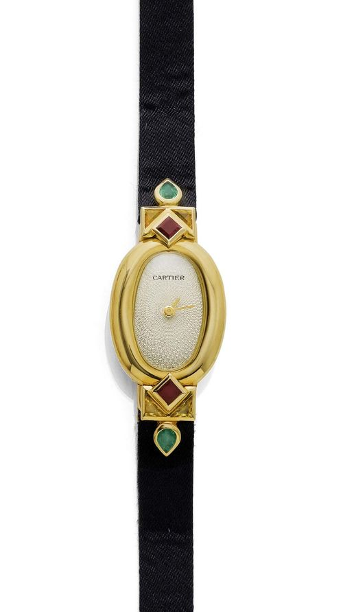 "RUBY AND EMERALD LADY'S WRISTWATCH, CARTIER BAIGNOIRE, 1990s. Yellow gold 750. ""Mini-Baignoire"" model. Oval, slightly convex case No. GC10127, with screw-down back, attaches set with 2 square-cut rubies, 4 triangle-cut sapphires and 2 drop-cut emeralds weighing ca. 1.00 ct. Fine, engine-turned dial with gold-coloured hands. Quartz movement. Black satin band with fold-over clasp. D 34 x 18 mm. With case, warranty, and setting tool, November 1994."