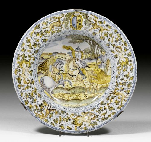 MAIOLICA PLATTER 'CACCIA AL LEONE',Castelli d'Abruzzo, workshop of Francesco Grue, circa 1660-70. Painted with a lion hunt in the tradition of Antonio Tempesta (1555 Florence 1630), dominated by a European and two Oriental hunters on horseback, the rim with coat of arms, probably of the 'Marchesi di Quinzi di l'Aquila'. D 29 cm. Provenance: - Oscar Bondy collection, Vienna. - Restituted in 1948 to the collector's heirs. - Blumka Collection, New York - Sotheby's New York, European Works of Art from the Private Collection and Gallery of the Blumka Estate, 9th-10th January 1996, Lot 37. - Kunsthandel Segal, Basel. - Private collection, Geneva.