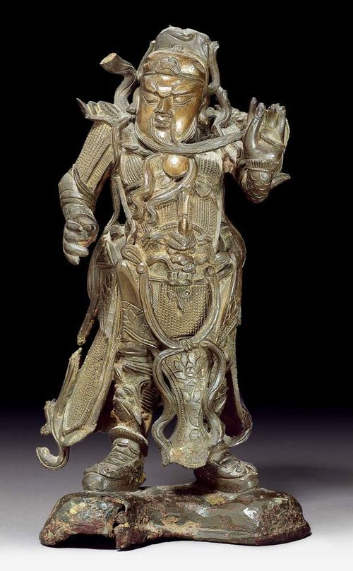 GUAN DI.China, Ming Dynasty, H 29 cm. Bronze. Vivid depiction of the general in full armour stroking his beard while frowning. Damaged scarf.