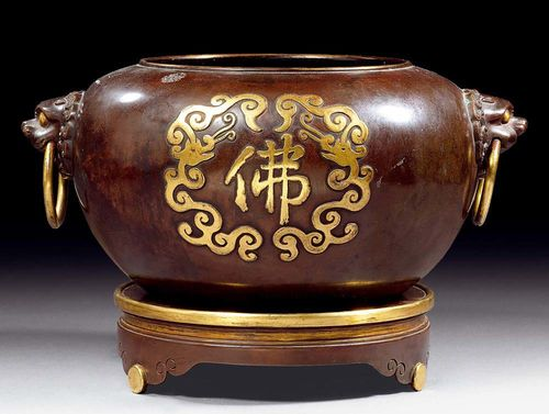 "LARGE INCENSE BURNER ON A STAND.China, 18th century. D (including handles) 35 cm. Dark,  patinated copper with two gilded ""fo"" (Buddha) characters in a stylized dragon surround on the outer wall. There are lion heads with ring-shaped handles on both sides. Matching stand on three legs. Seal mark."